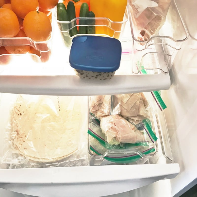 Food grouped in containers to keep the fridge organized.