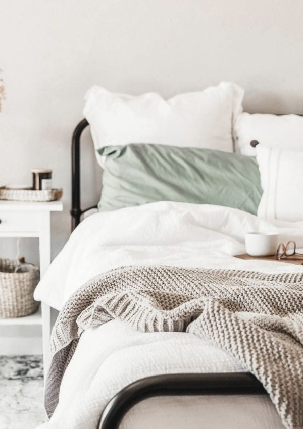Unmade bed with white bedding and a green pillow.