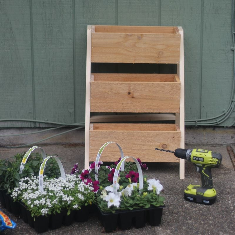 3 tiered wood planter box getting ready for new flowers.  A drill ready to drill draining holes.