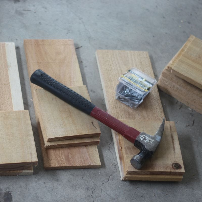 cedar planks cut down to size, nails, and a hammer.  Ready to assemble the cedar planter box.