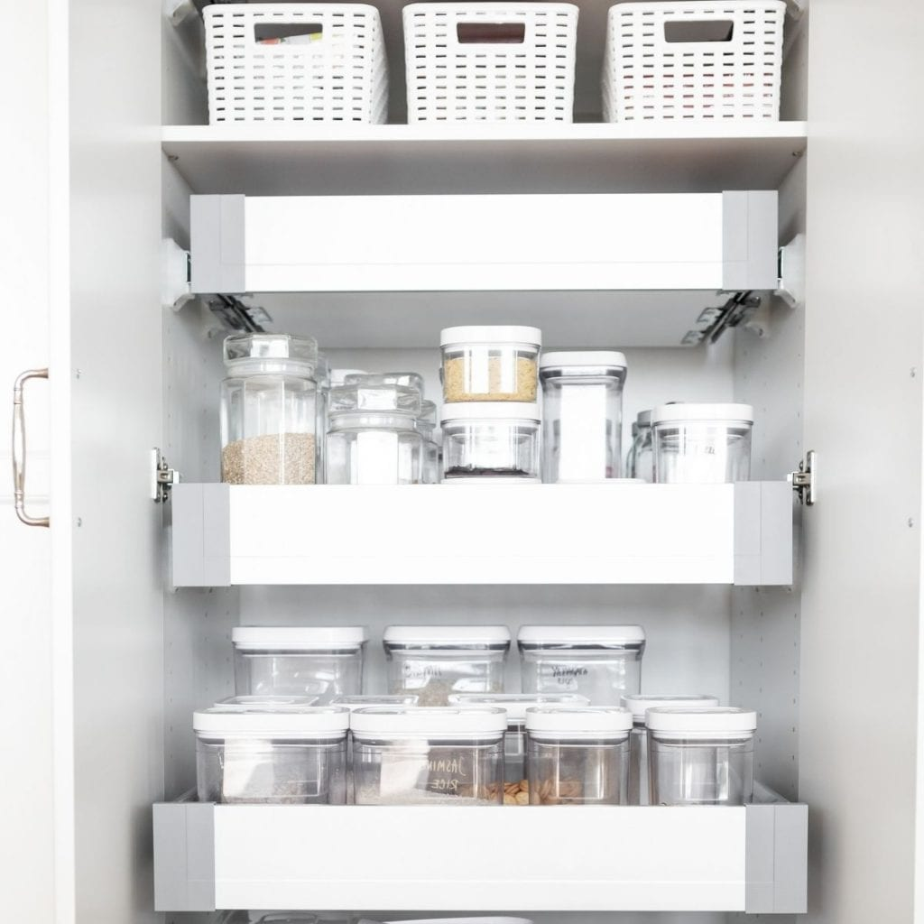 a small pantry organized with containers and baskets