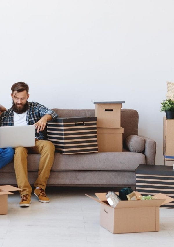 living room with moving boxes and people on a couch with a laptop looking at that laptop.