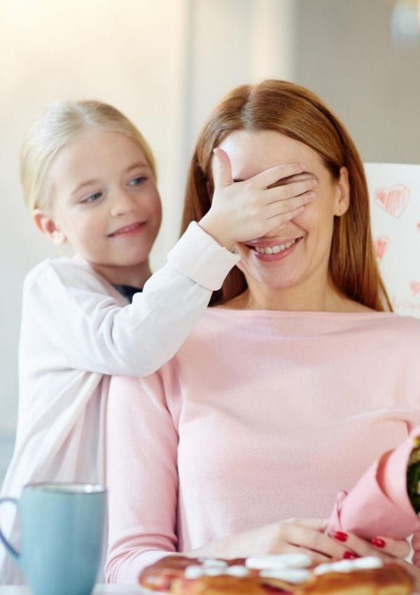 child covering her mom's eyes