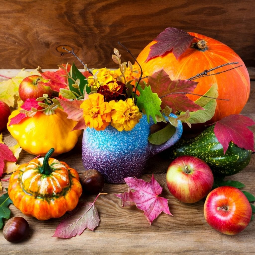 pumpkins, leaves, and apples on a table