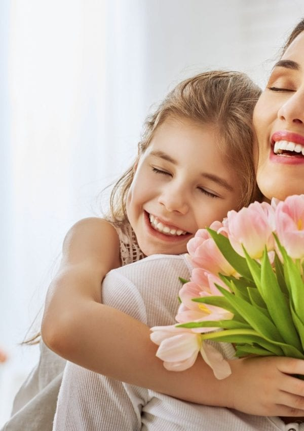child holding flowers hugging her mom.