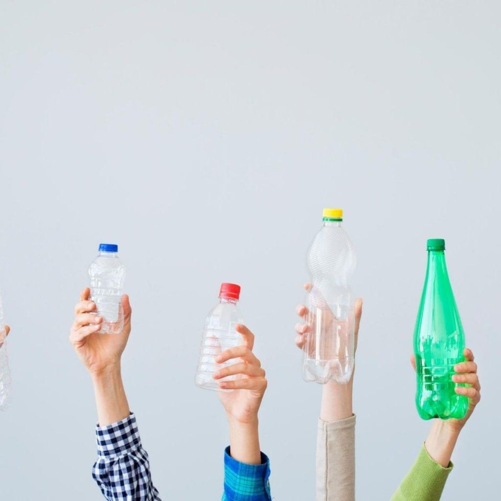 holding empty plastic bottles