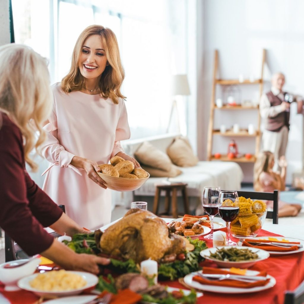 2 woman setting the table for thanksgiving dinner
