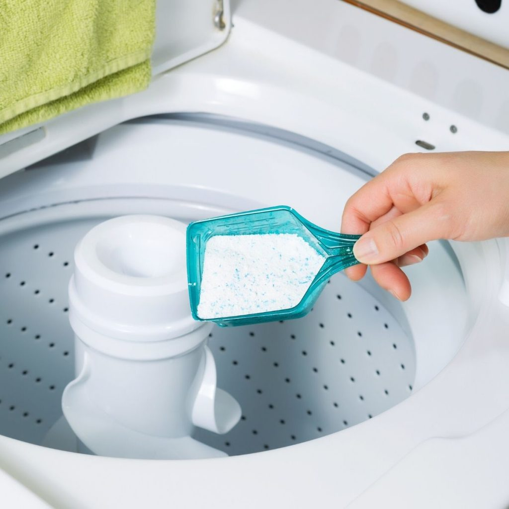 pouring laundry soap into a washer