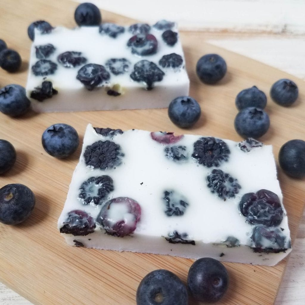 homemade soap with dried blueberries on a board with fresh blueberries