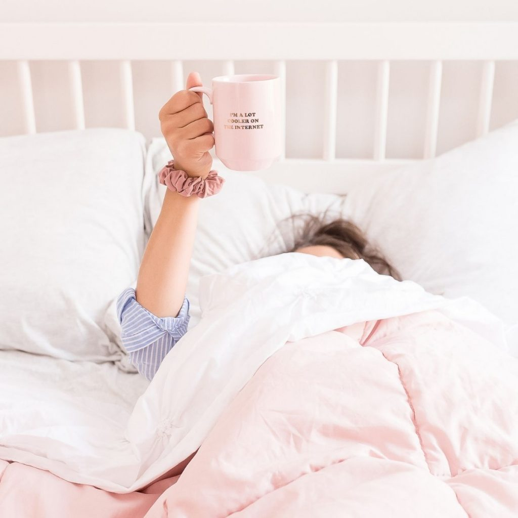 women in bed holding a cup of coffee