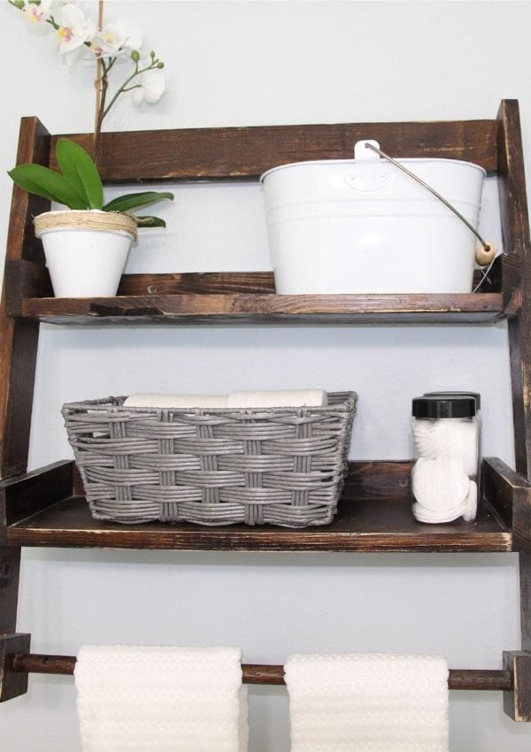 over the toilet shelf with baskets and towels