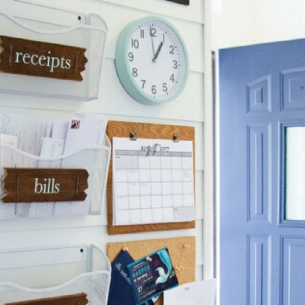 file folders on the wall to organize receipts and bills.  There's a clock and wall calendar to keep the whole family organized.