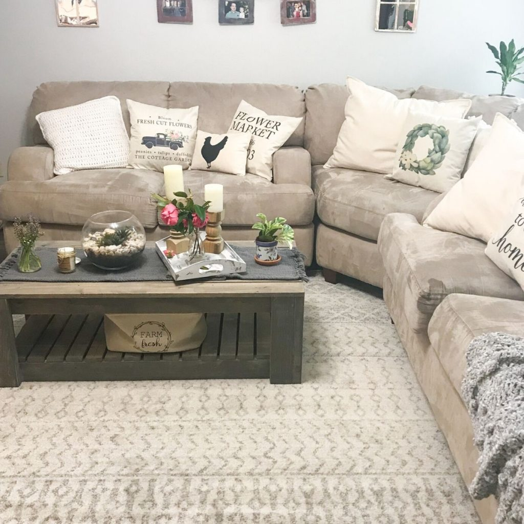 family room showing a sectional couch with farmhouse pillows a coffee table with flowers and candles.