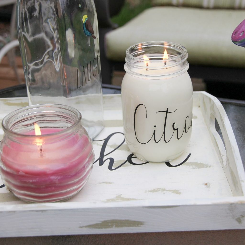 2 citronella lit candles on a wooden tray sitting on an outdoor glass coffee table.