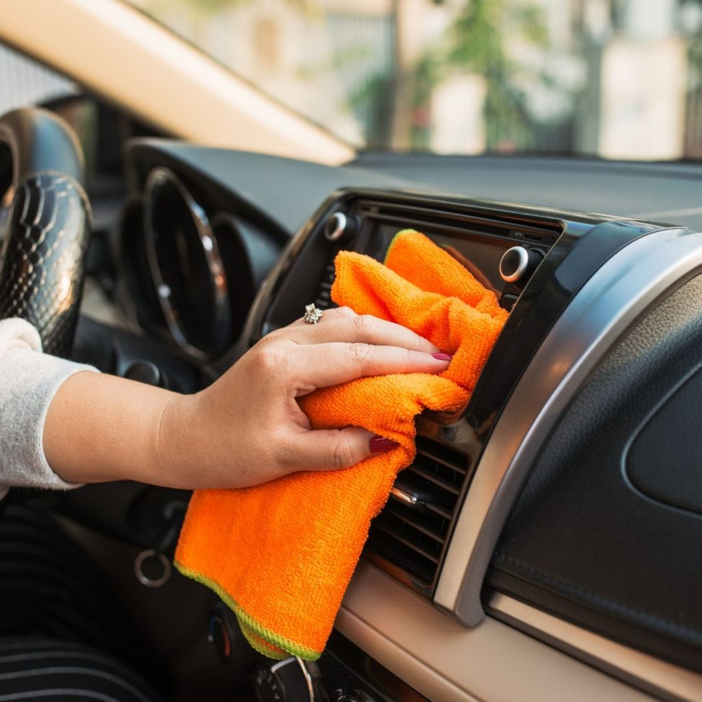 Cleaning dust from the interior of the car.