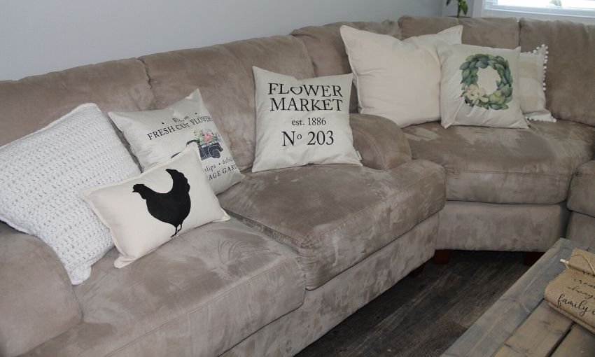 A sectional couch with pillows.