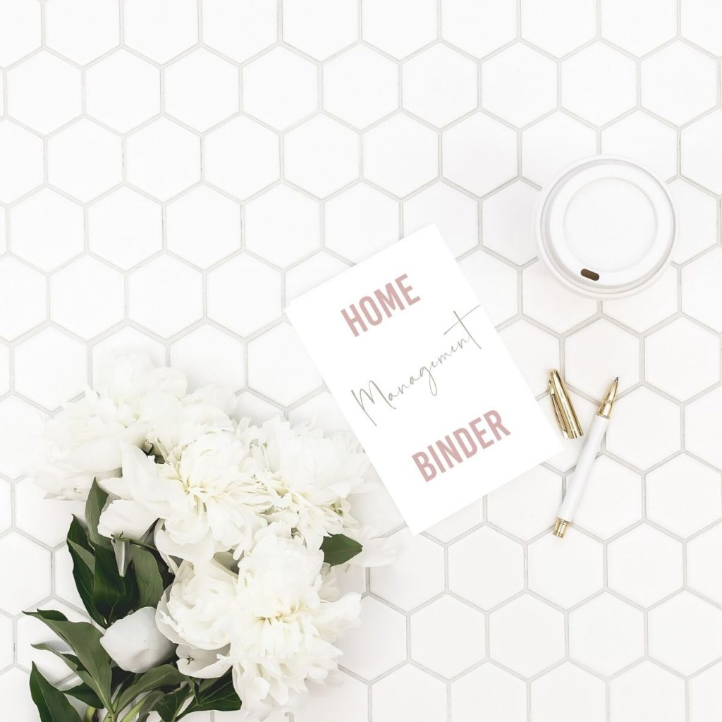 Home management binder pdf on a white table with flowers, a pen, and cup of coffee.