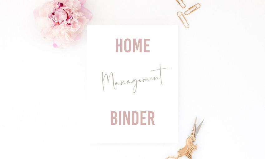 home management pdf on a counter with paper clips, scissors, and a flower.