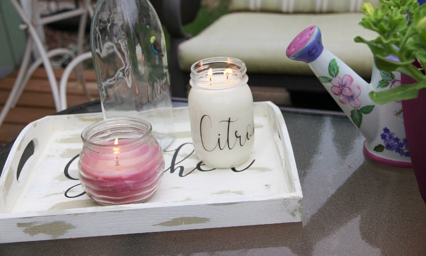 2 lit citronella candles on a wooden tray sitting on a outdoor coffee table.