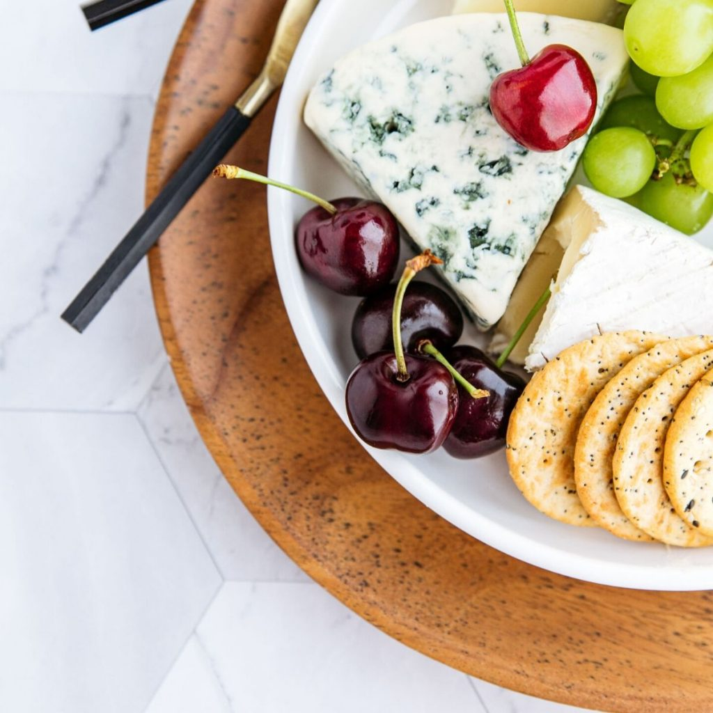 Cheese, crackers, and fruit on a plate with a cheese knife.