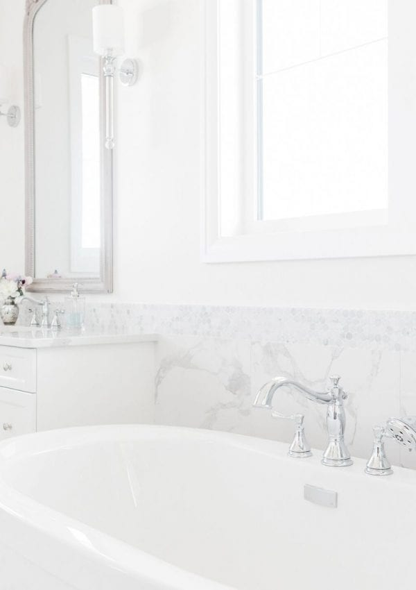 An image of a white and marble bathroom a white tub and white vanity with a mirror and wall sconces.