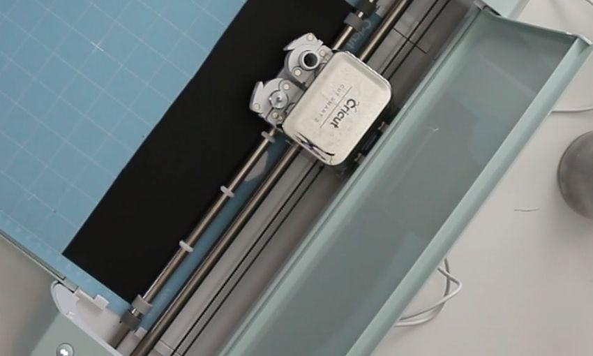 show Cricut cutting machine cutting a piece of black vinyl.