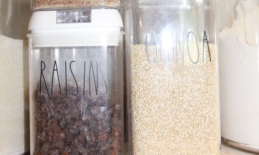 shown raisins and quinoa in plastic containers labeled in the pantry.