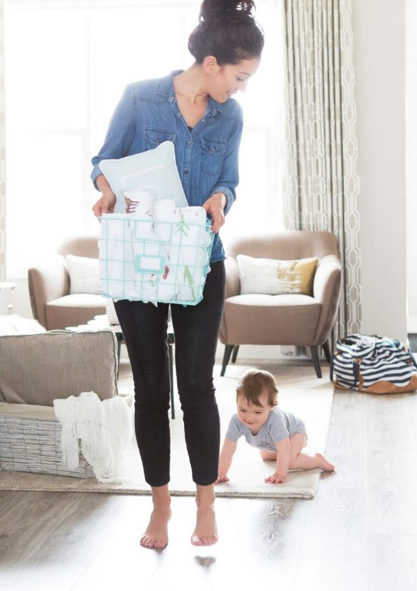 mother caring a basket while her child crawls on the floor of a living room.