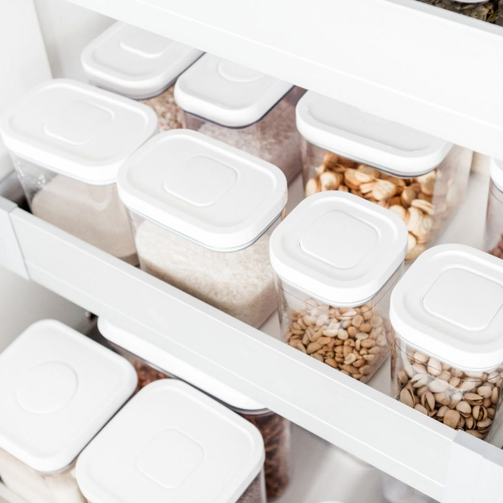 Pantry drawers organized with plastic containers.