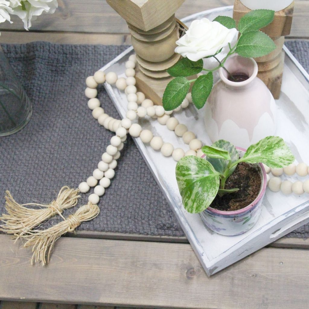 2 wooden bead garland with tassels on a table with a wooden tray, potted plant, rose in a vase, and 2 candles on wooden candle sticks.