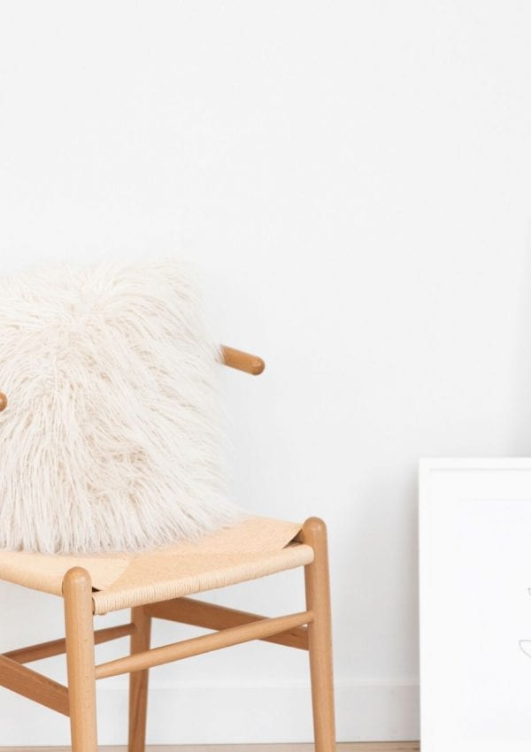 wooden chair with a pillow against a blank wall with a photo leaning against the wall.