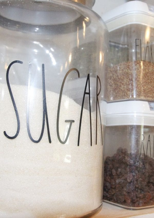 Sugar, flax meal, and raisins in the pantry labeled with pantry labels.