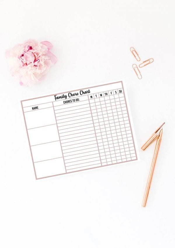 chore chart free printable on a table with a pen, 3 paper clips, and a peoni.