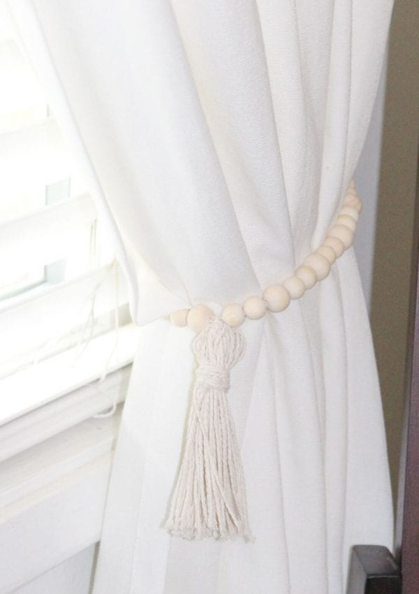 wooden curtain tie backs with a tassel holding back white curtains.