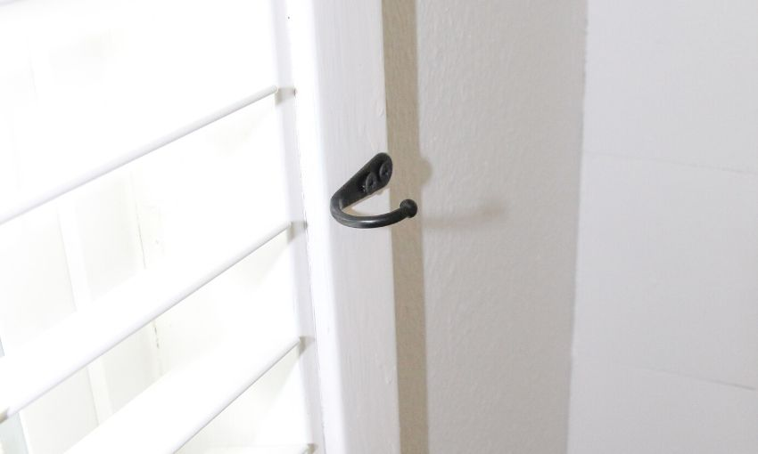 Black hook on the side of a window with white trim.