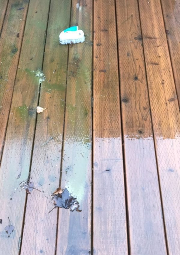 a wooden deck with moss and grime on the left with a scrub brush and a freshly clean deck on the right.