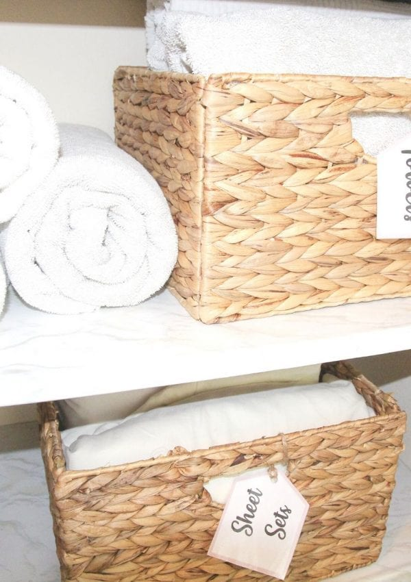 a linen closet with rolled white towels and baskets filled with sheet sets and towels.