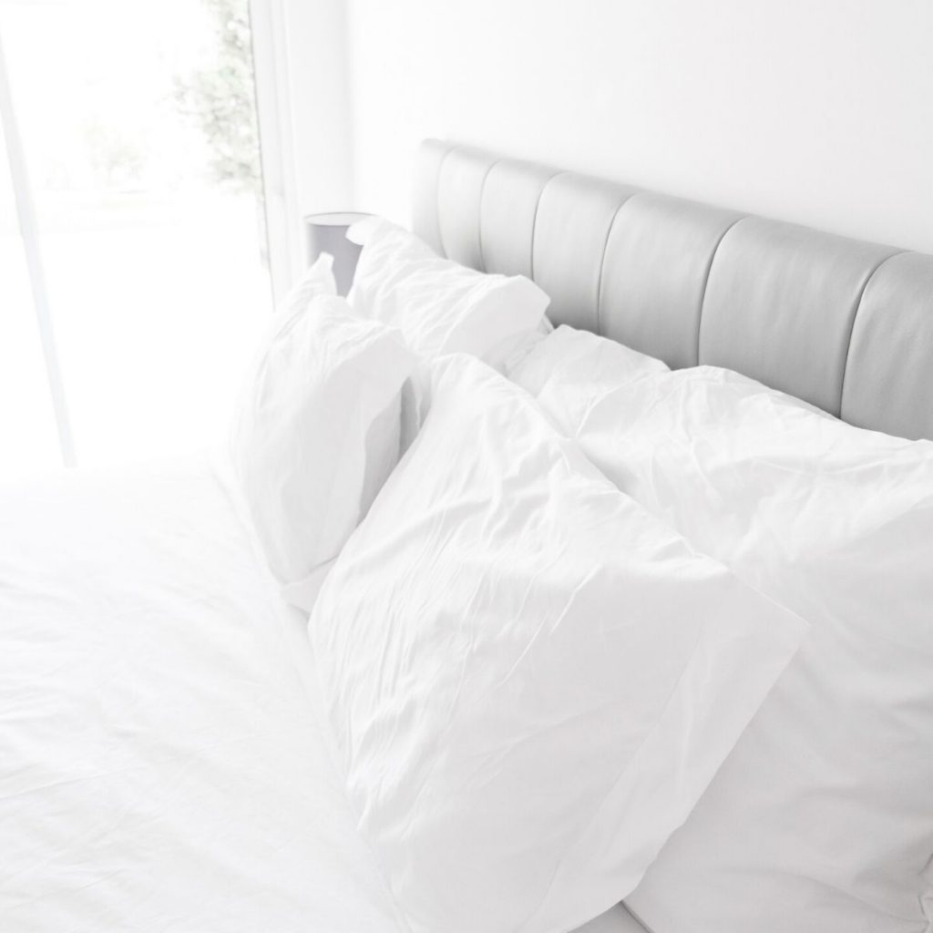 white pillows on a bed with a grey headboard and a white comforter.