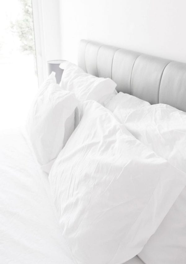 4 white pillows on a bed with a grey headboard and a sheet set with white comforter.