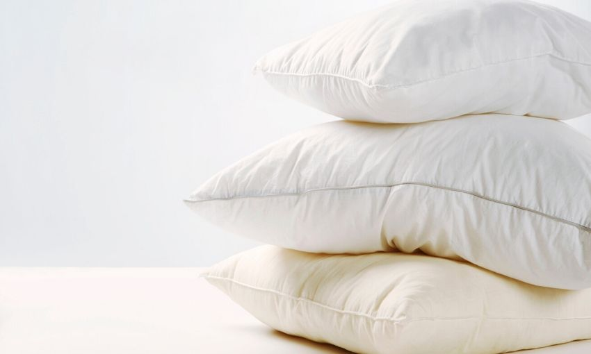 3 pillows stacked on a table without pillow cases on.