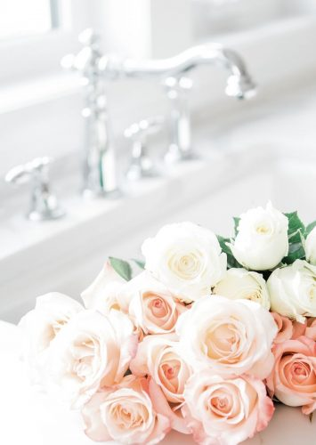 roses in a sink with marble counters and a chrome faucet.