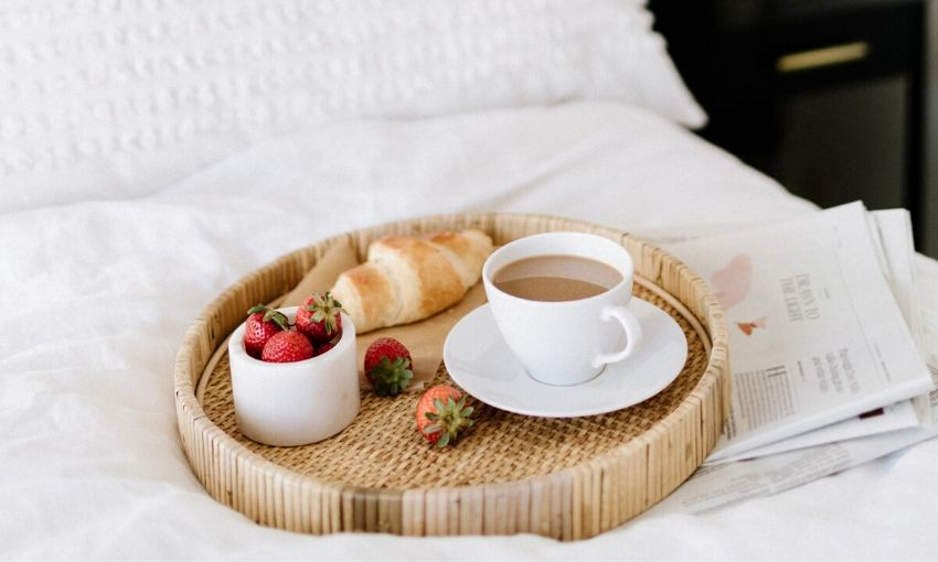 a basket with strawberries, a cup of coffee, and a pastry on a bed with a newspaper.