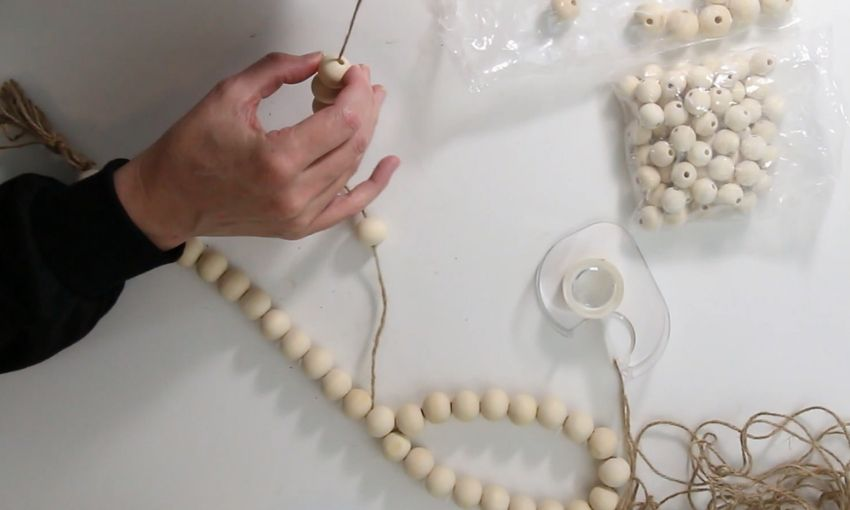 Stringing wooden beads onto a piece of jute a bag of wooden beads and some tape are on the white table.