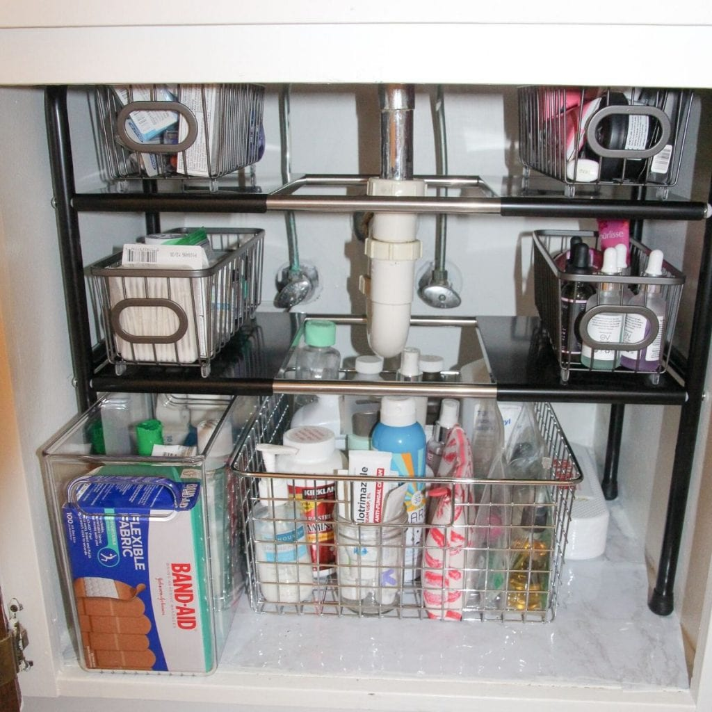 organized under the bathroom sink with baskets and a shelf