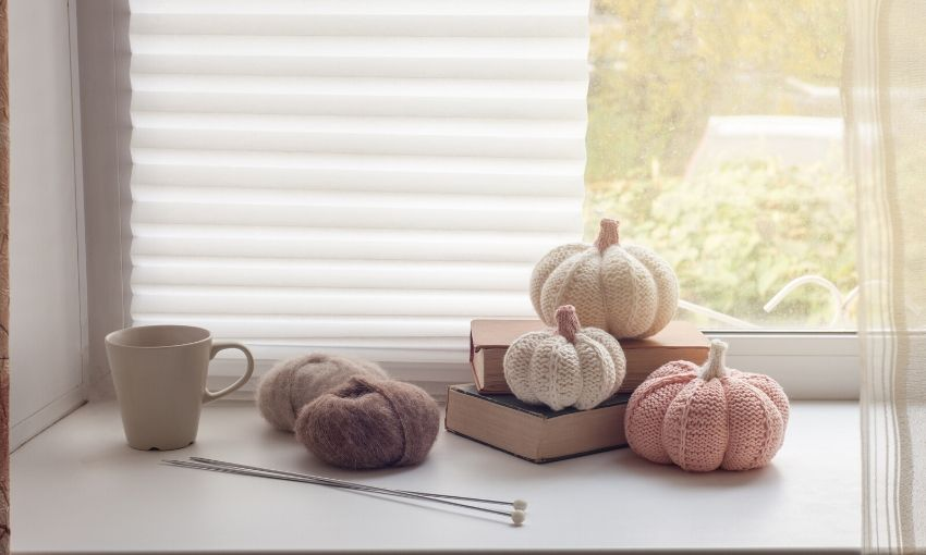 knitted pumpkins in an organized craft room.