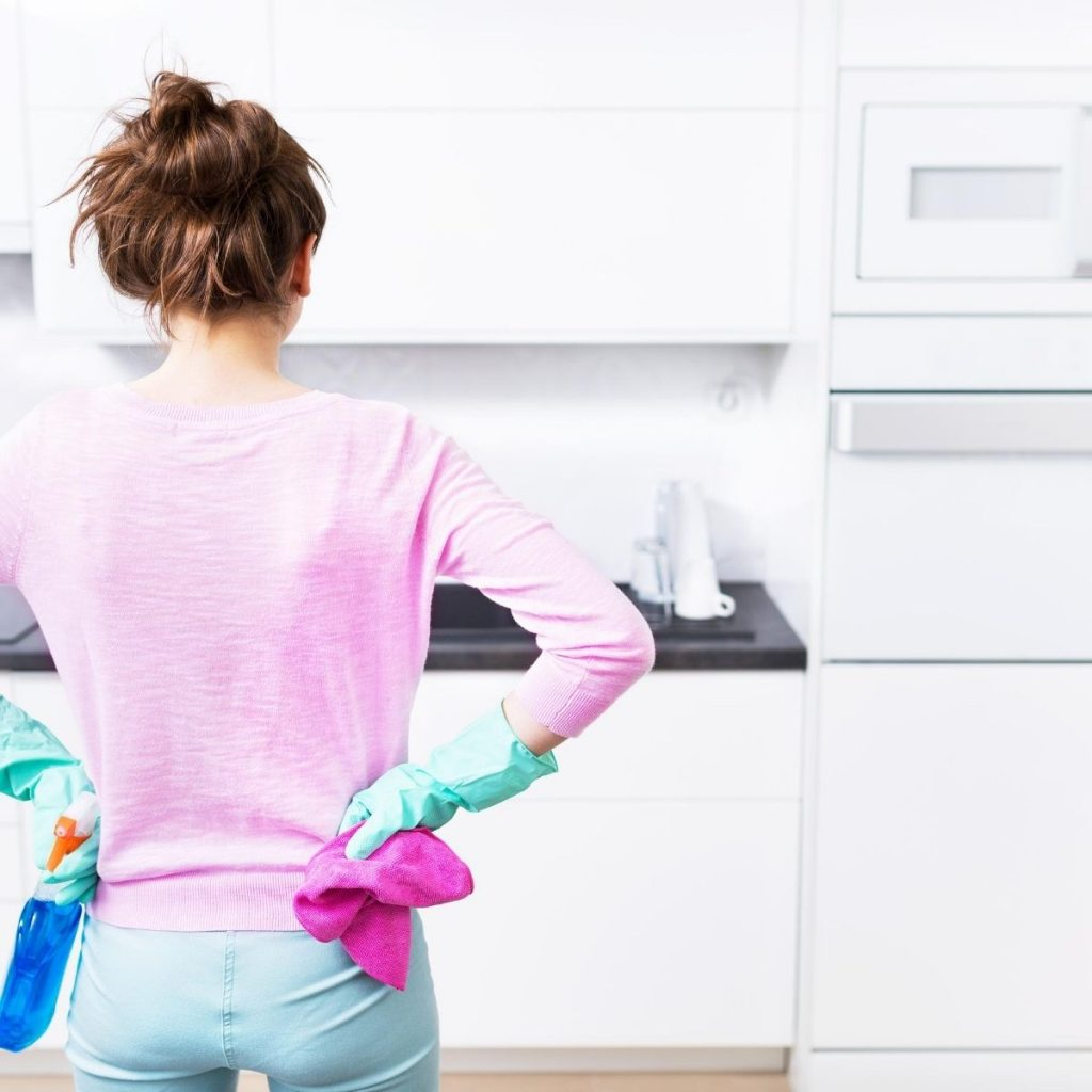 woman standing in the kitchen cleaning the most difficult spots in your home
