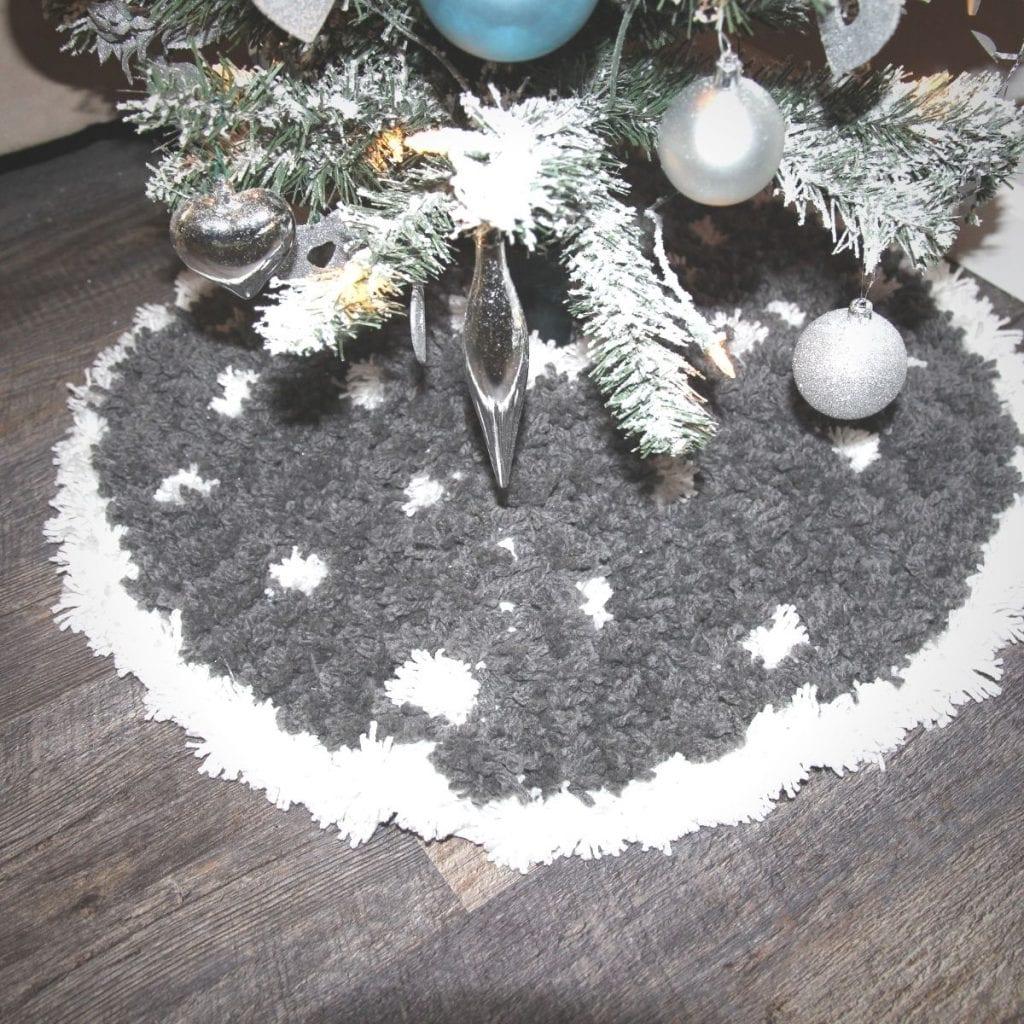 DIY Pom Pom Tree Skirt at the base of a Christmas tree