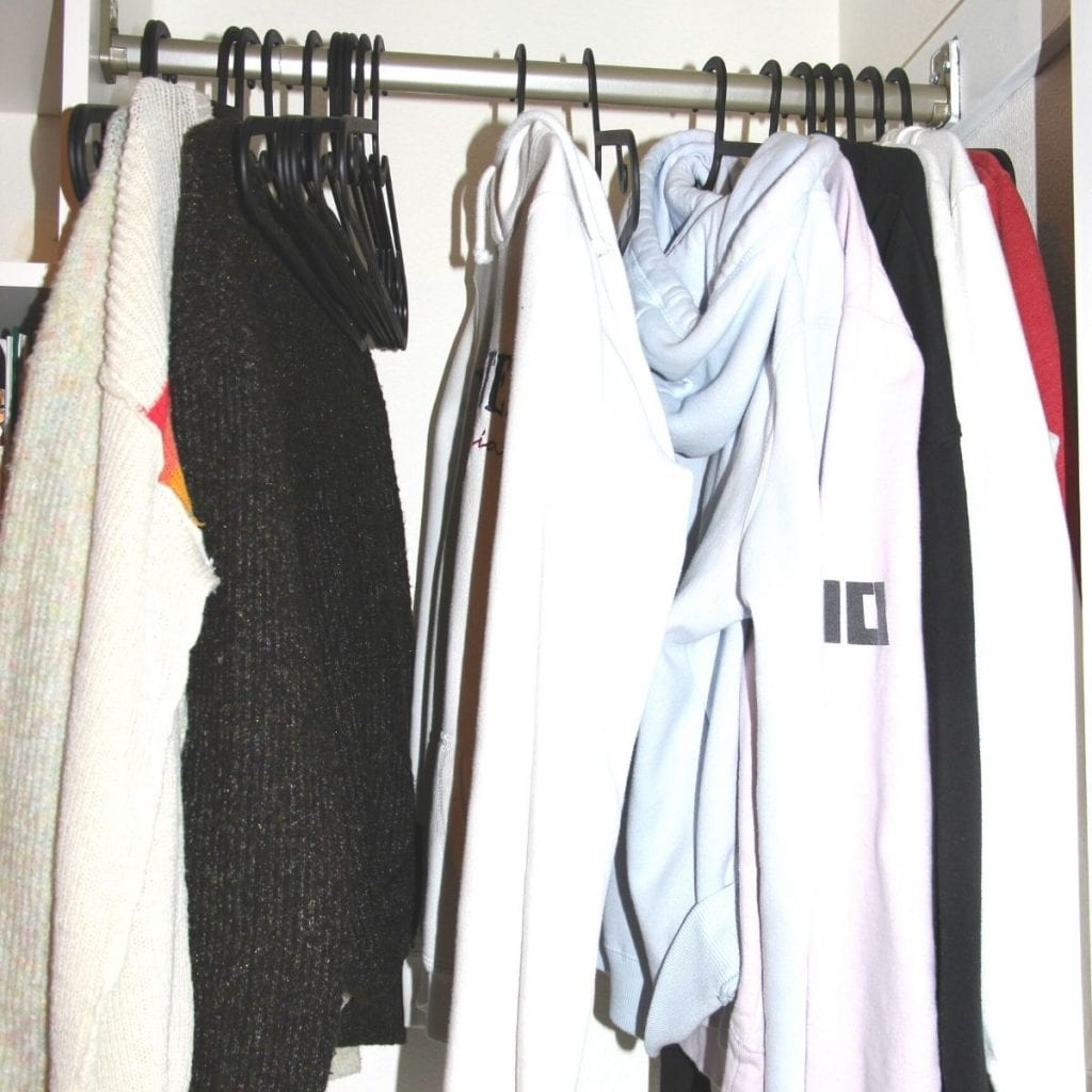 sweaters hanging in the closet