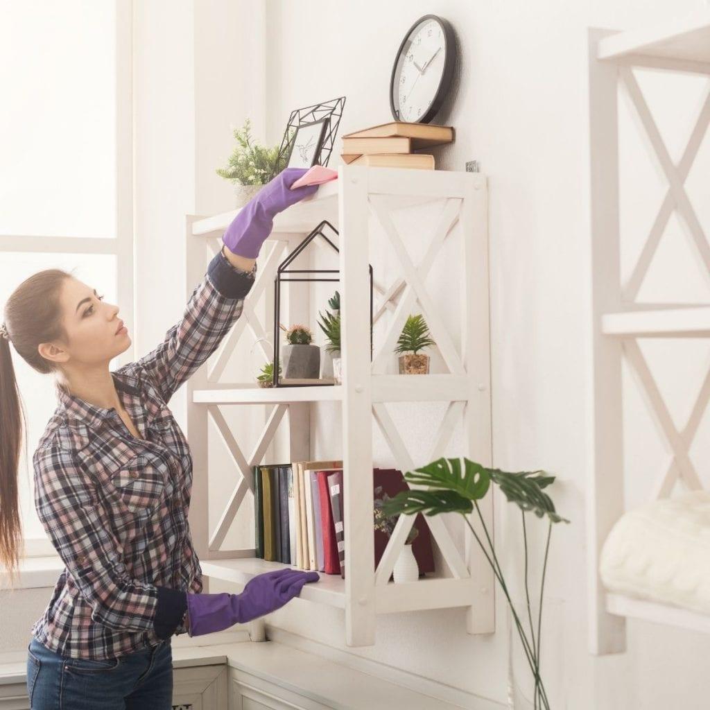 woman dusting a shelf