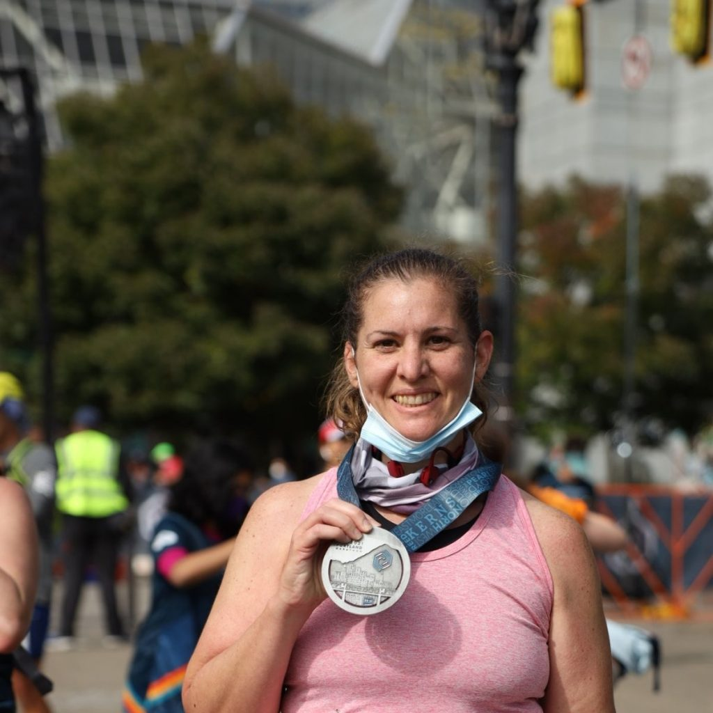Jenn holding up her finishing medal of the Portland marathon